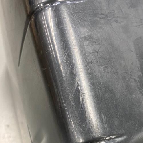 光沢のある鏡面仕上げの表面に傷がついたスーツケース