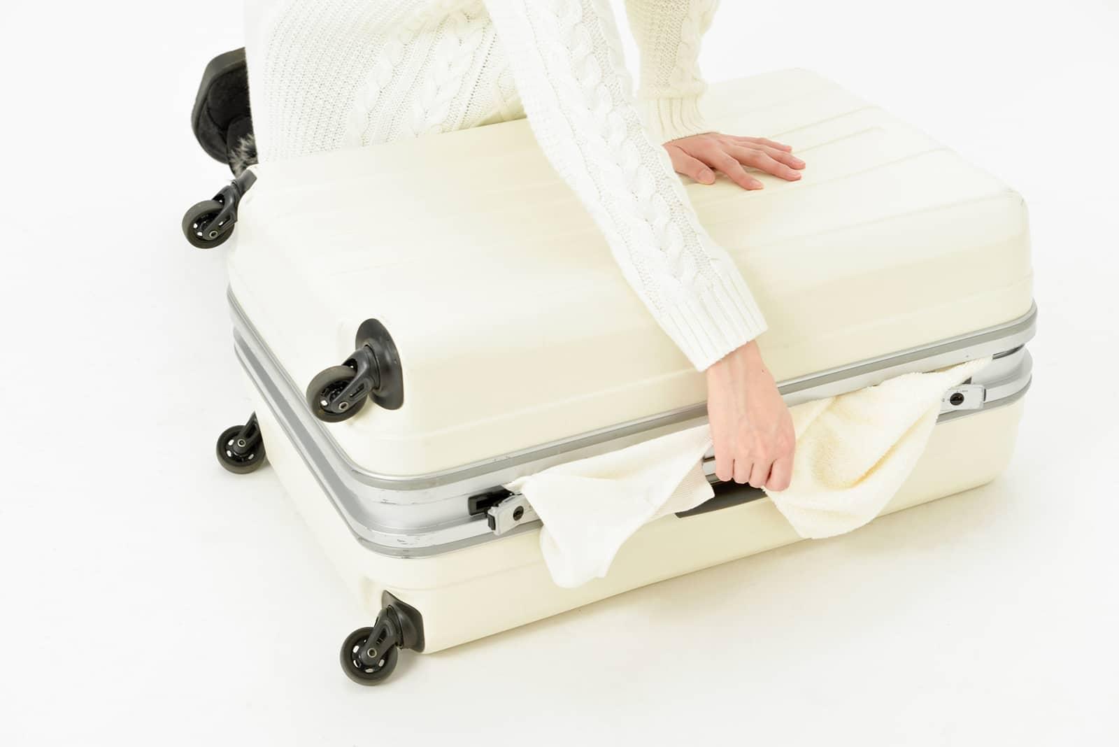 スーツケースから荷物がはみ出している様子