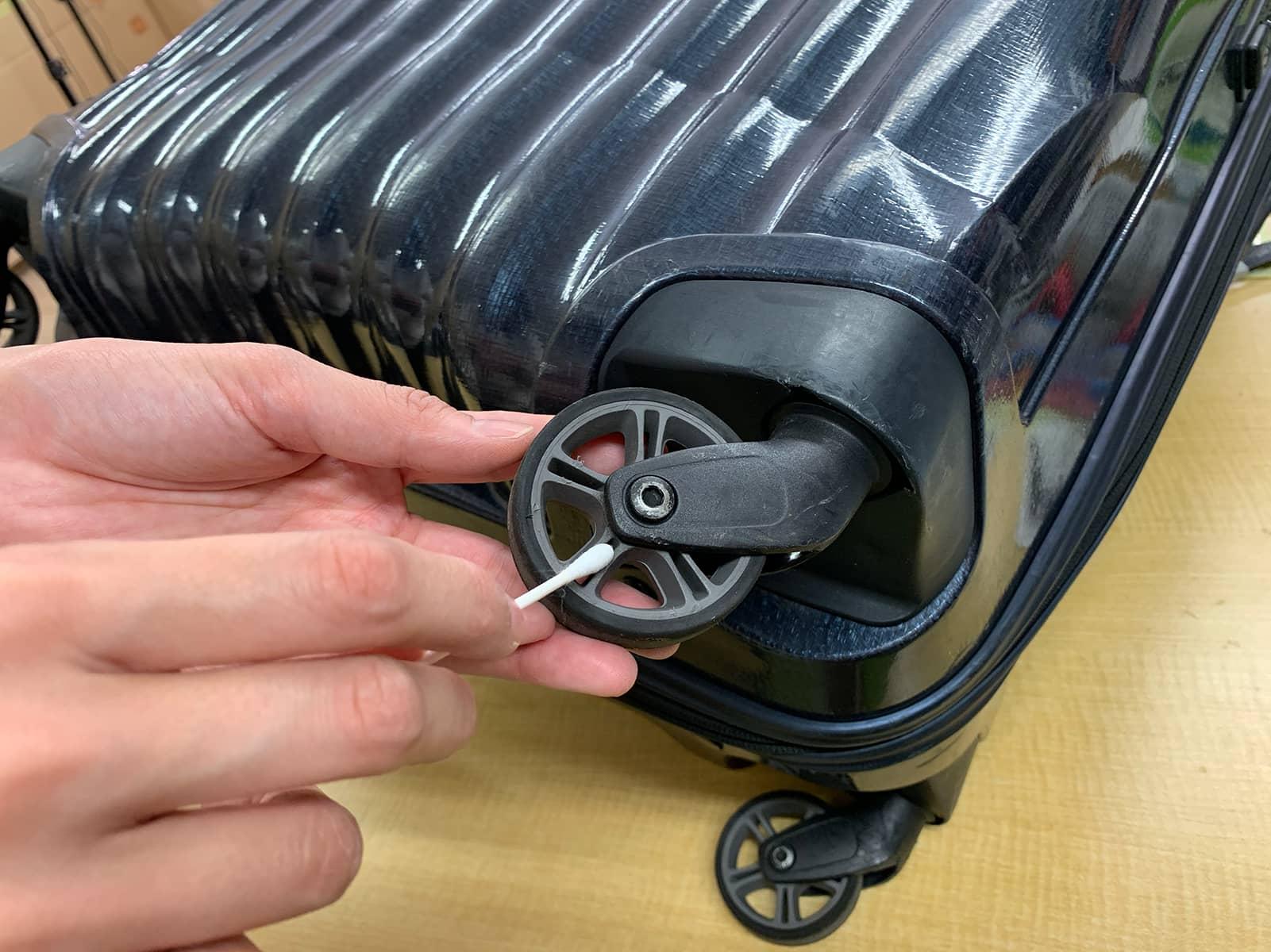 スーツケースのキャスターに絡まったゴミや埃を綿棒で取り除いている様子