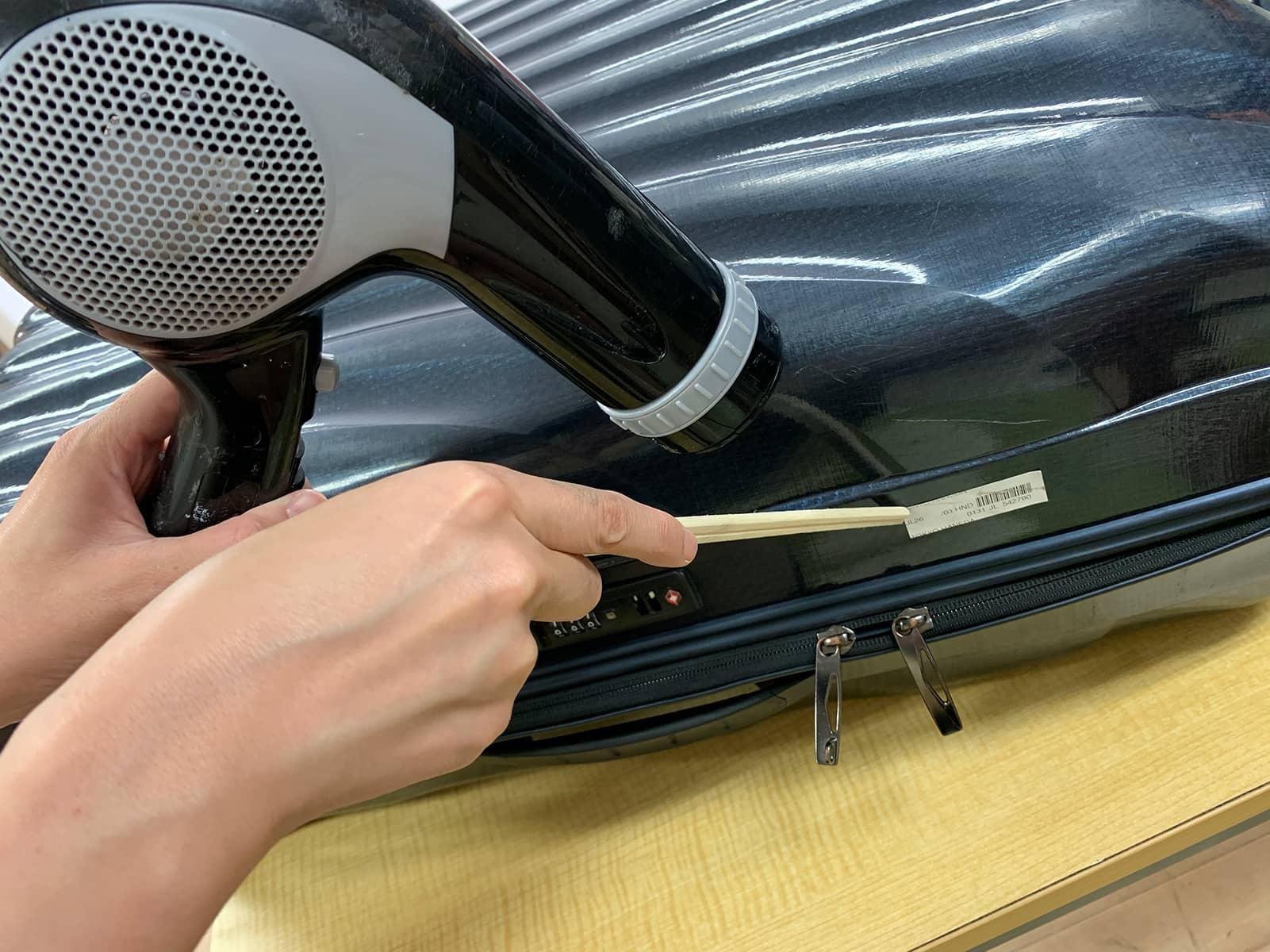 スーツケースに貼られたシールに、ドライヤーの熱風を当てながら、割り箸を使って剥がしている様子