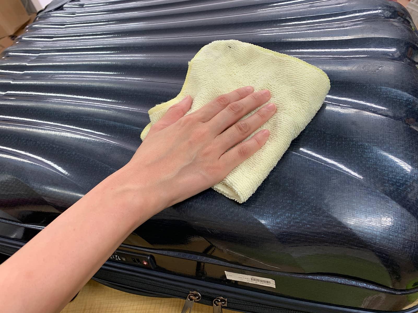 スーツケースのボディの汚れを布で拭いている様子