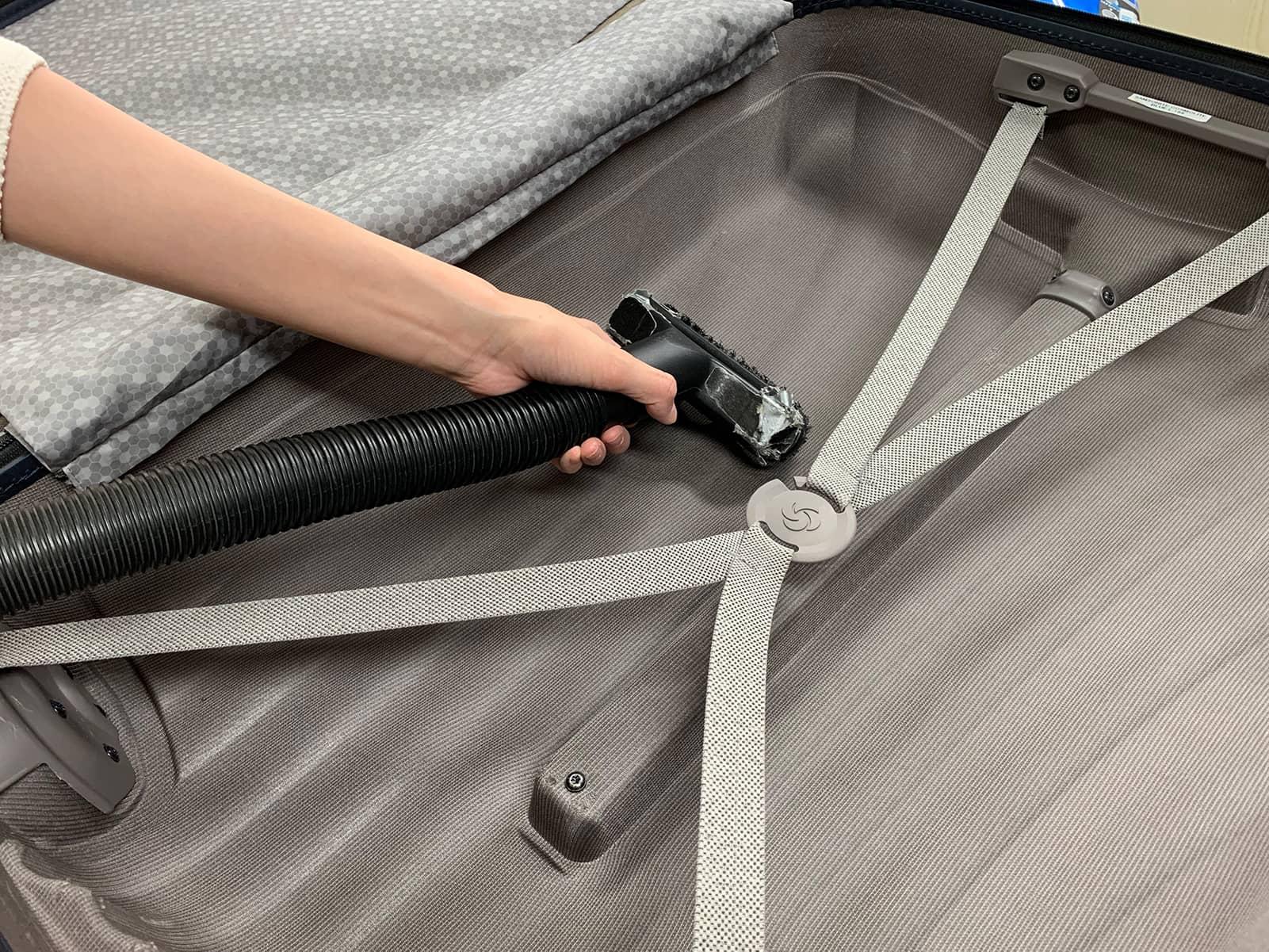 スーツケースの内装に溜まった髪の毛や埃を掃除機で吸い取っている様子