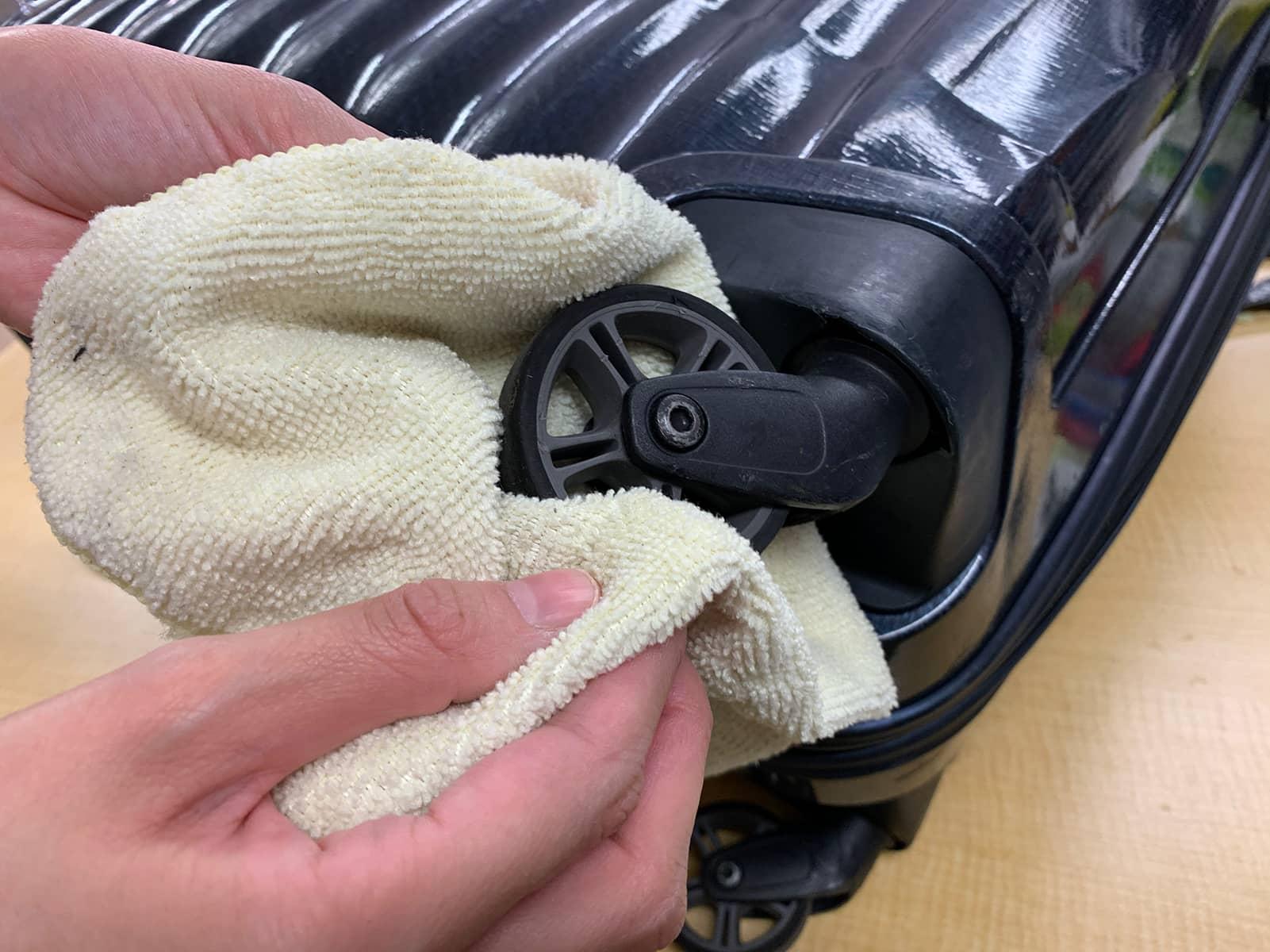 スーツケースのキャスターを布で拭いている様子