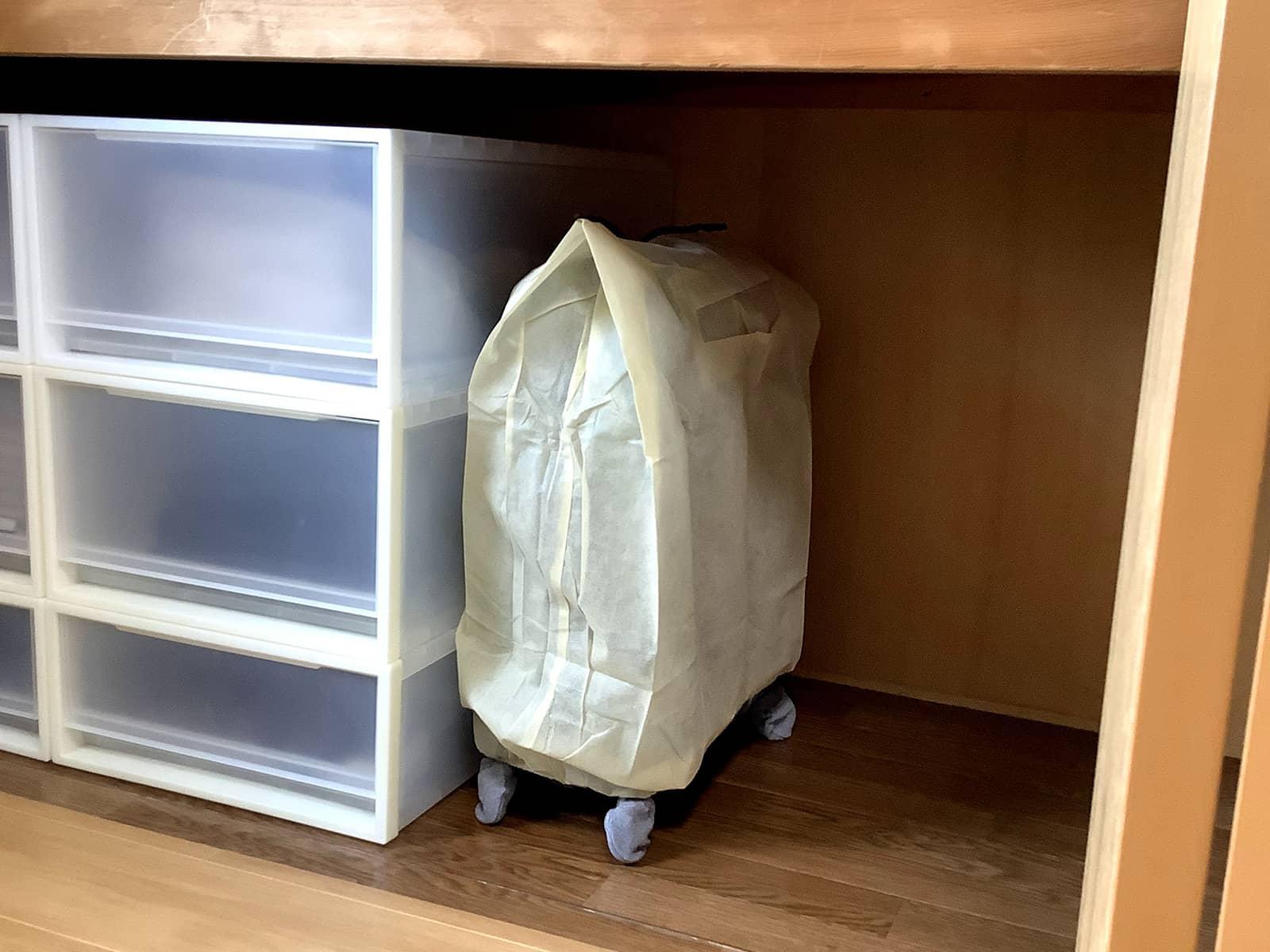 スーツケースカバーをかけて保管されているスーツケース