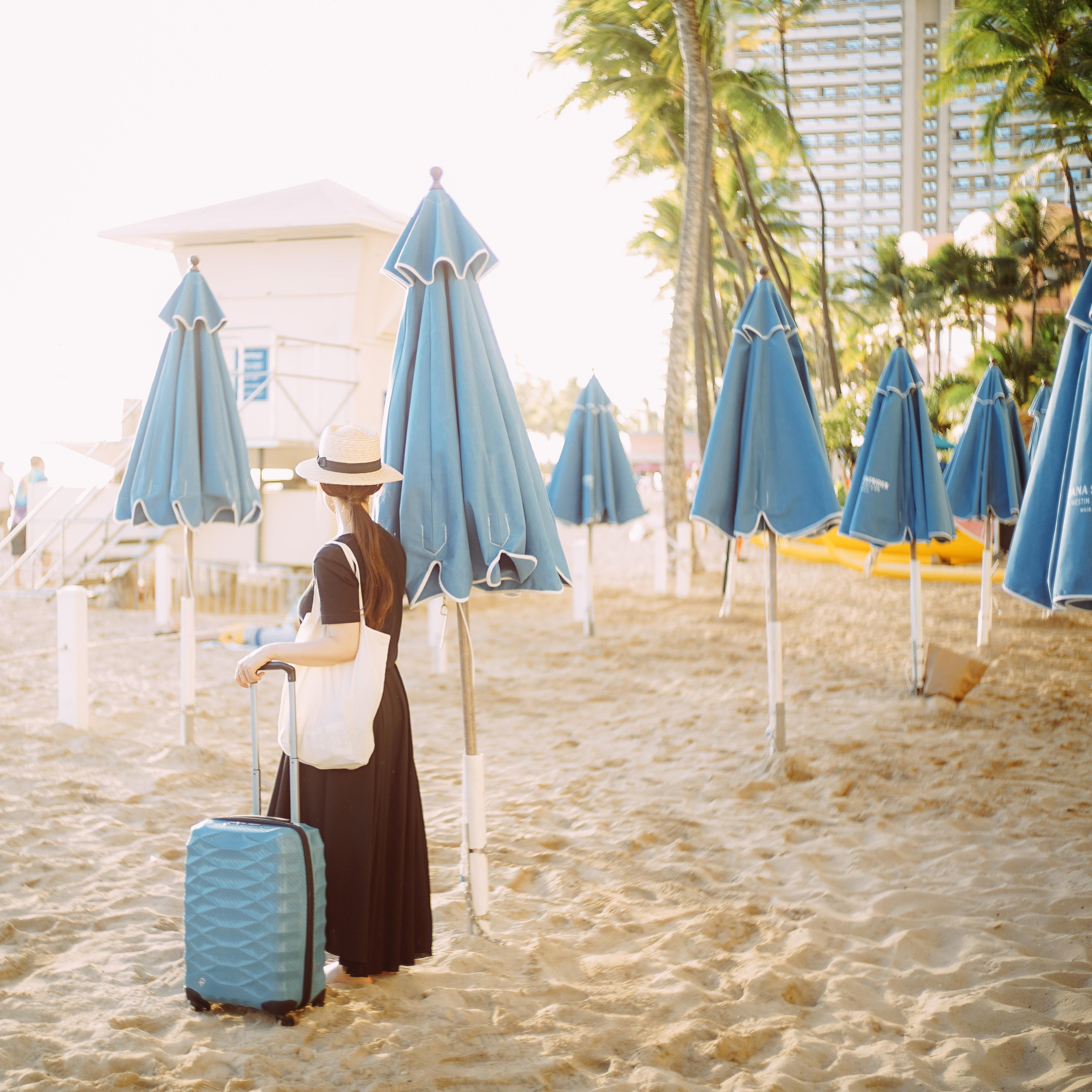 水色のスーツケースを持つ女性