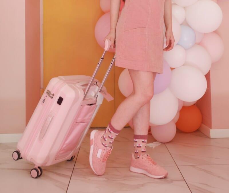 ピンクのスーツケースを引く女性