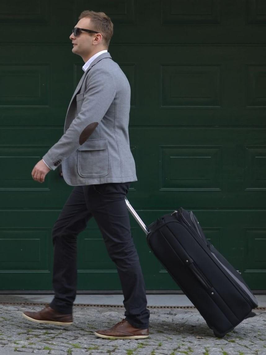 凹凸のある道路でスーツケースを引く男性