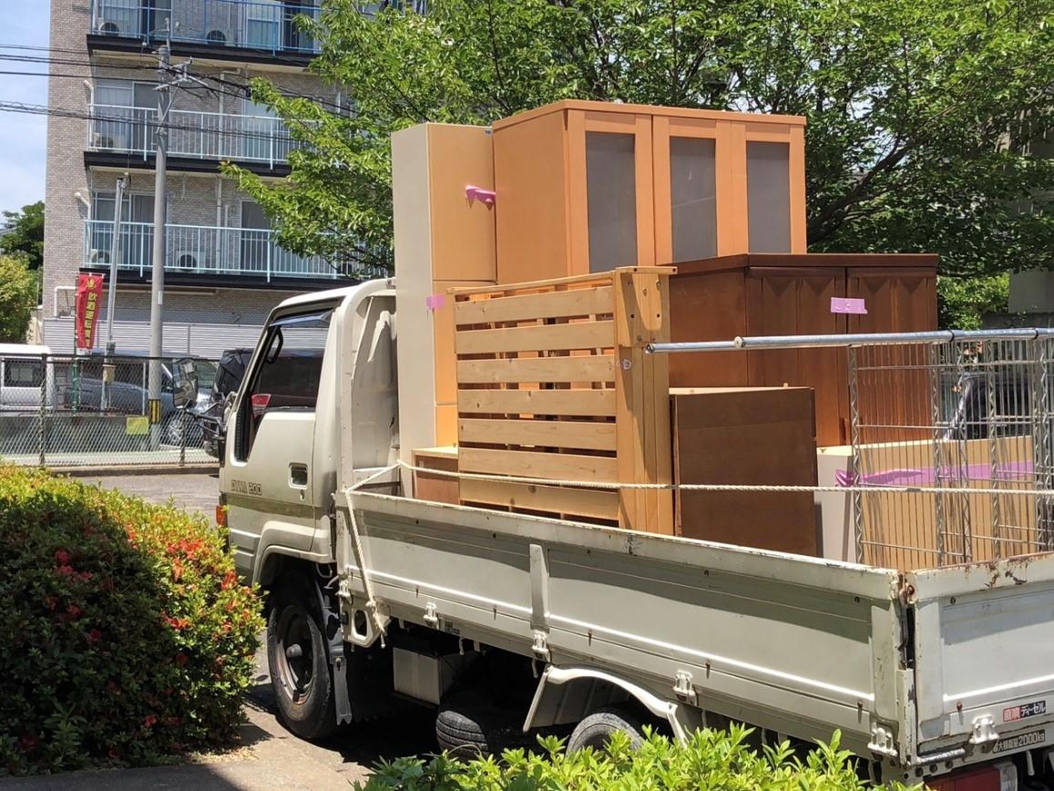 不用品回収業者を利用。不用品回収業者のトラックの荷台にタンスや食器棚が積まれている。