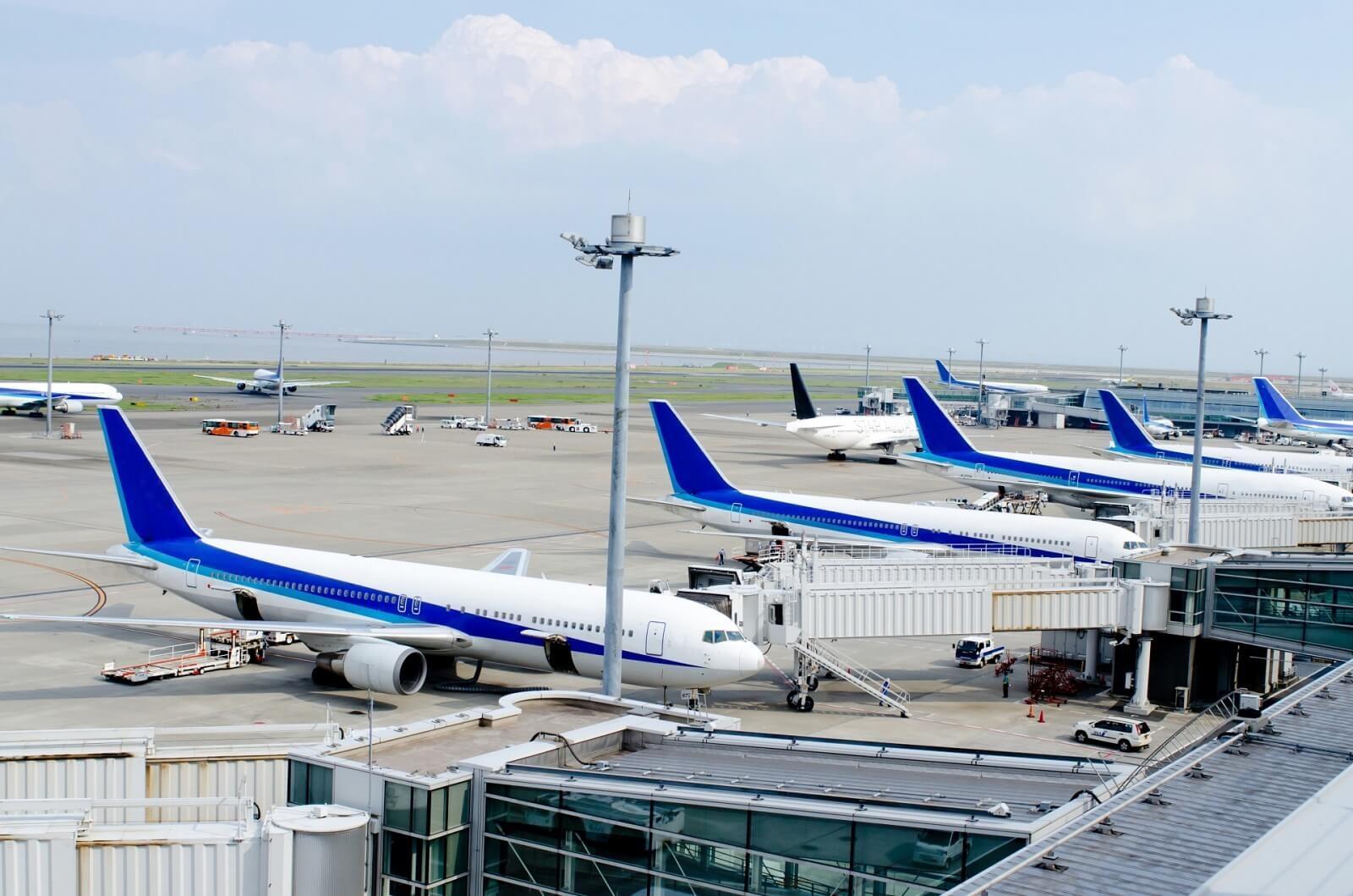 飛行機での出張の注意点。空港に飛行機が並ぶ描写。