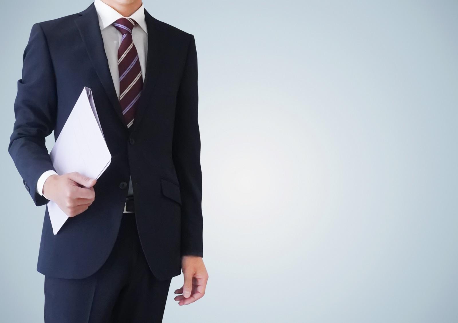 男性の出張に必要な持ち物リスト。スーツを着た男性が立っている描写。