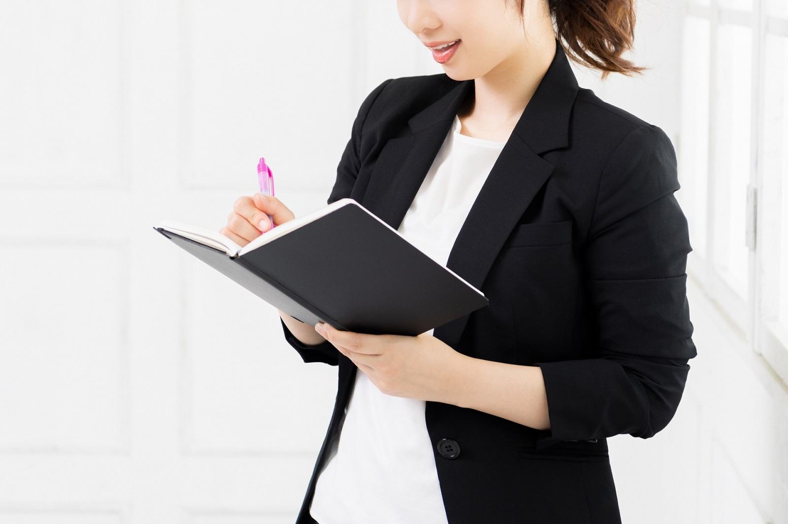女性の出張に必要な持ち物リスト。スーツを着た女性が手帳に書き込んでいる描写。