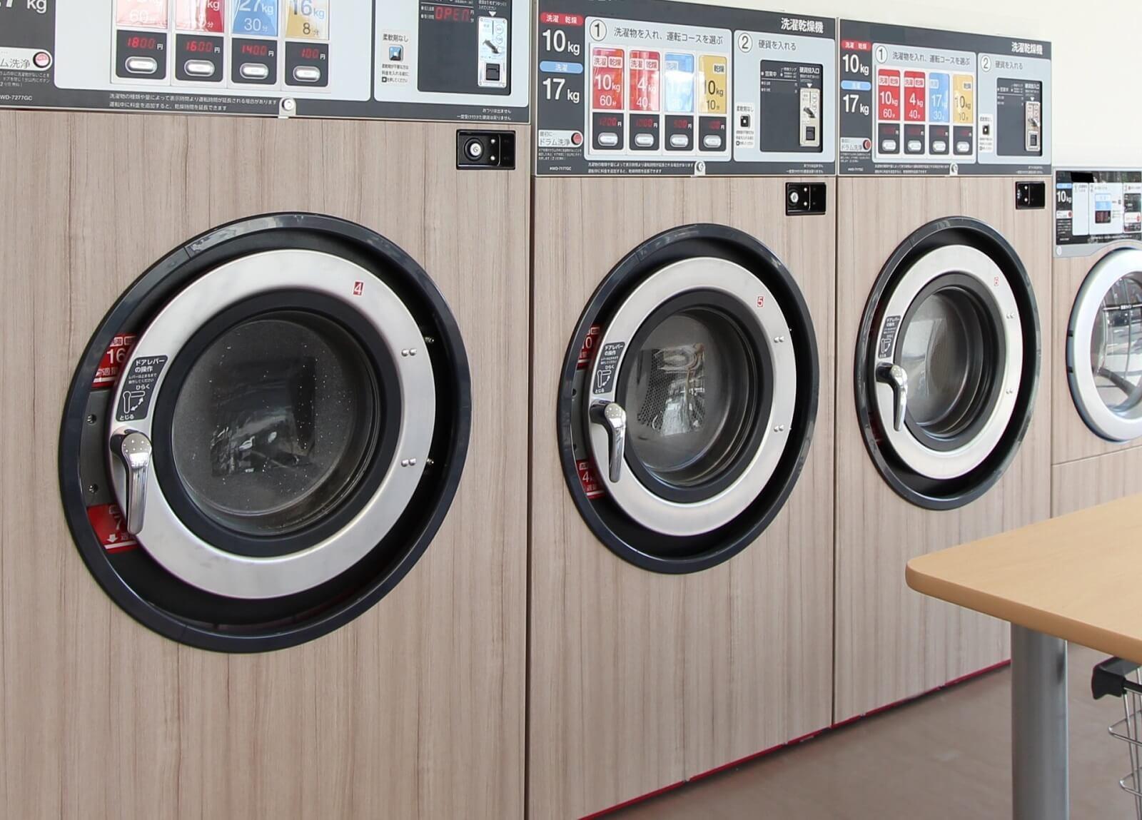 出張先のホテルのコインランドリーを使用して洗濯をする。コインランドリーの洗濯機が並んでいる描写