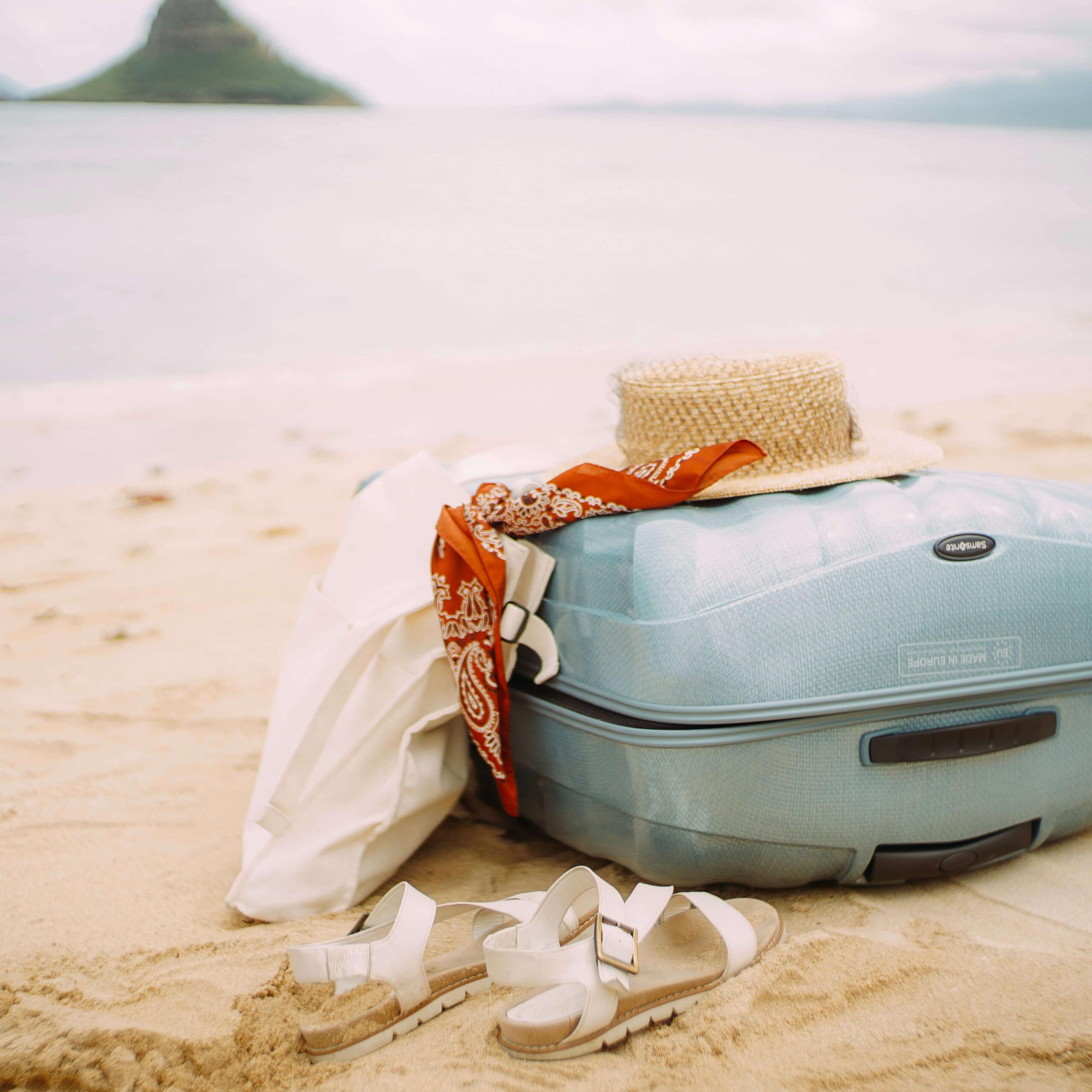 砂浜にある淡いブルーのスーツケース