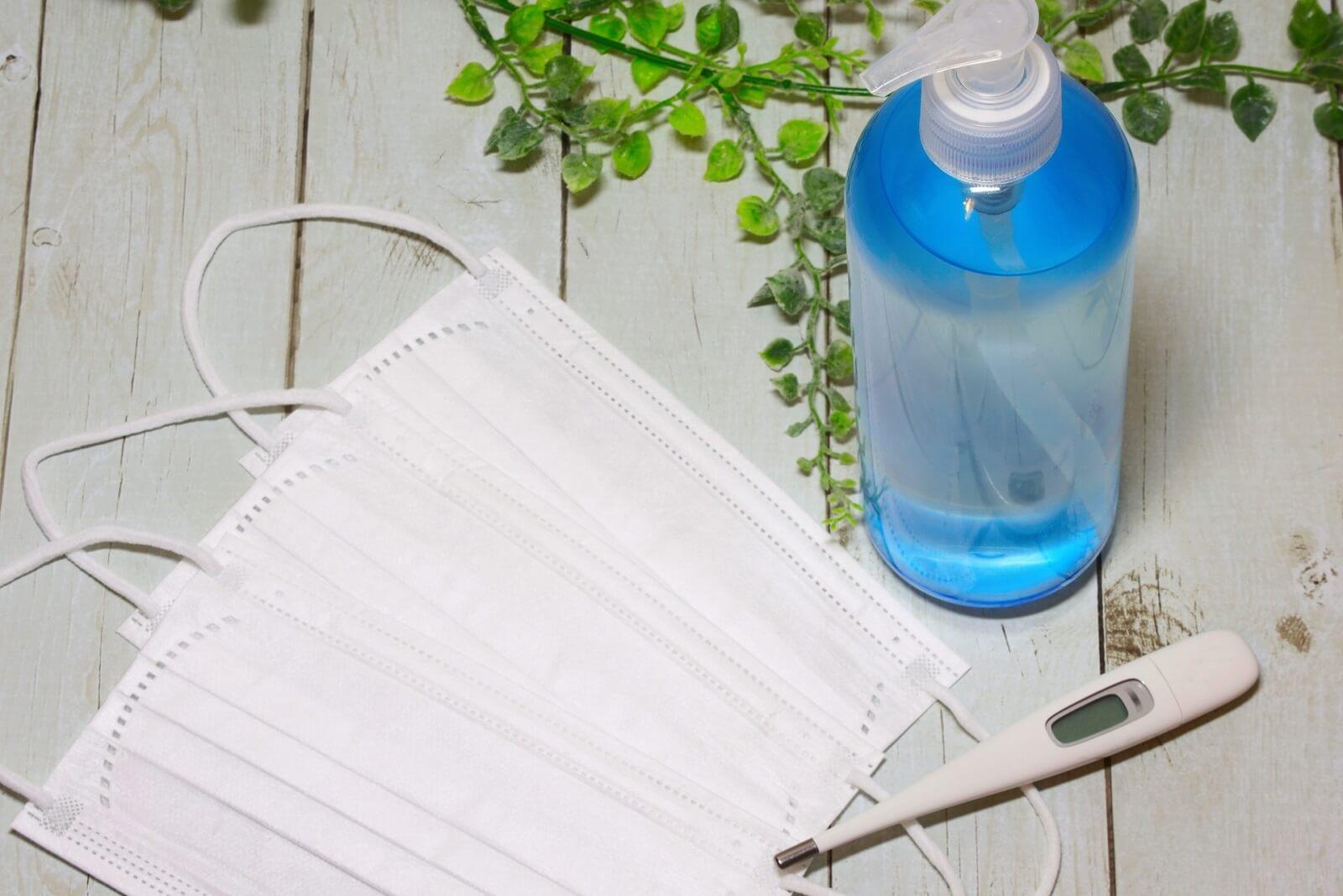 コロナ禍での感染対策に必要な物。使い捨てマスク、消毒液、体温計が並ぶ描写