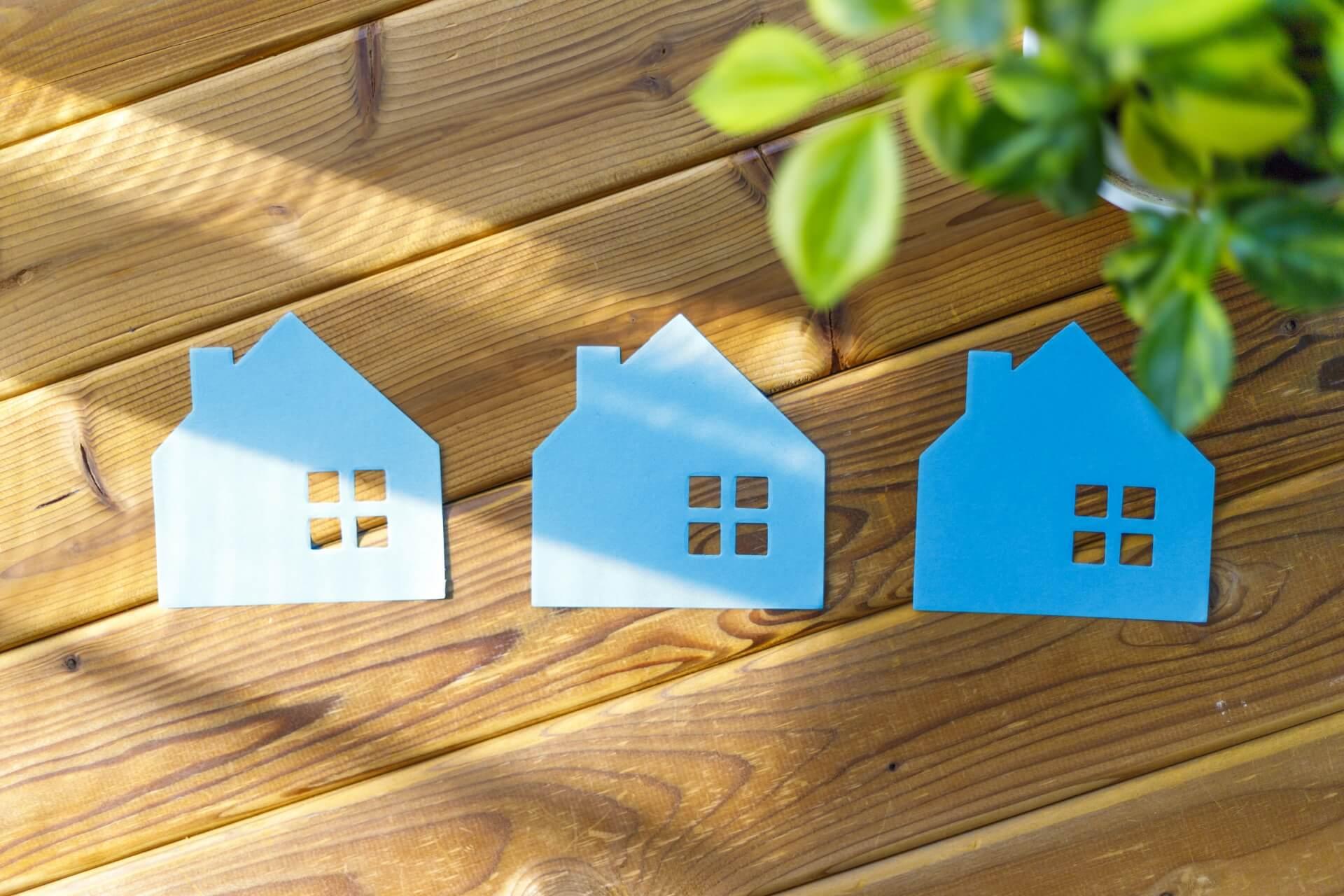 スーツケースを自治体で処分。 陽の当たるフローリングに青い折り紙で作られた家が3つ