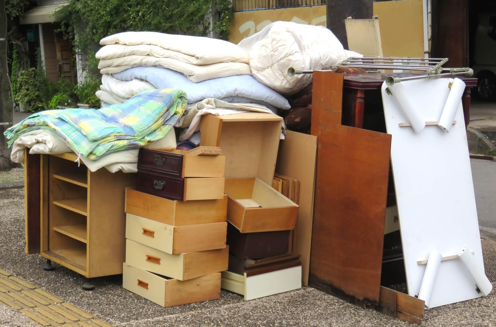 スーツケースを粗大ごみとして捨てる。布団やタンスが山のように積み上げられている