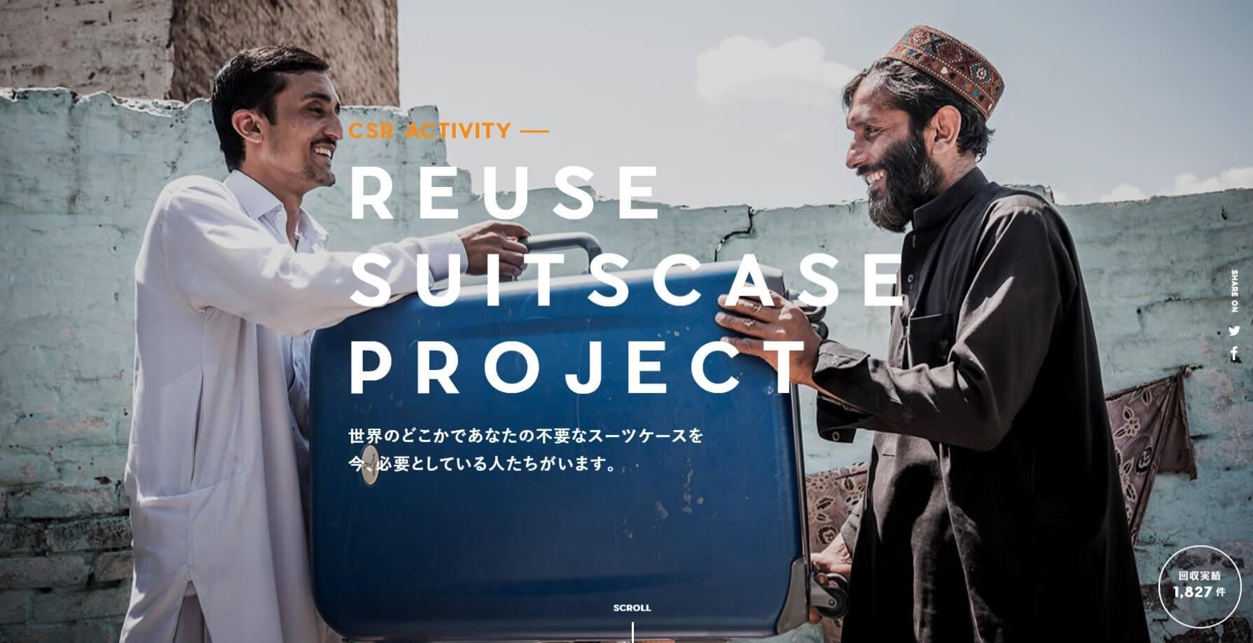 リユーススーツケースプロジェクト。 笑顔の二人の外国人男性。 一方の男性から使い込まれたスーツケースが手渡される。