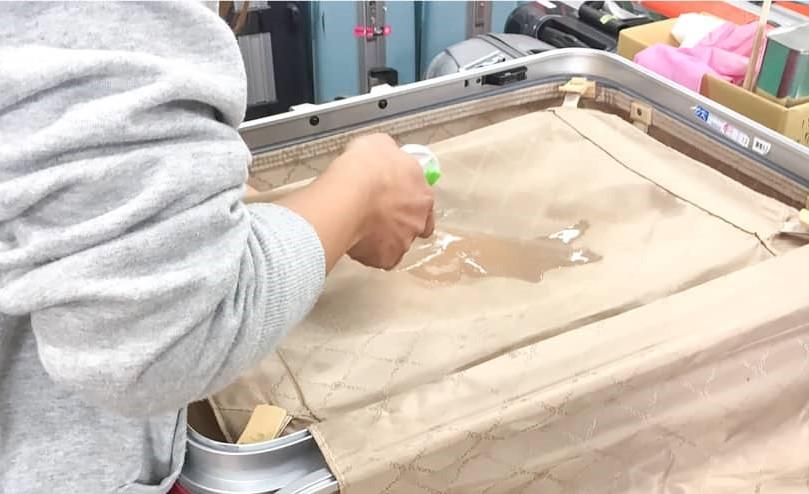 スーツケースの内装クリーニング。シミの箇所に液体を吹きかけて内装のシミ取り作業