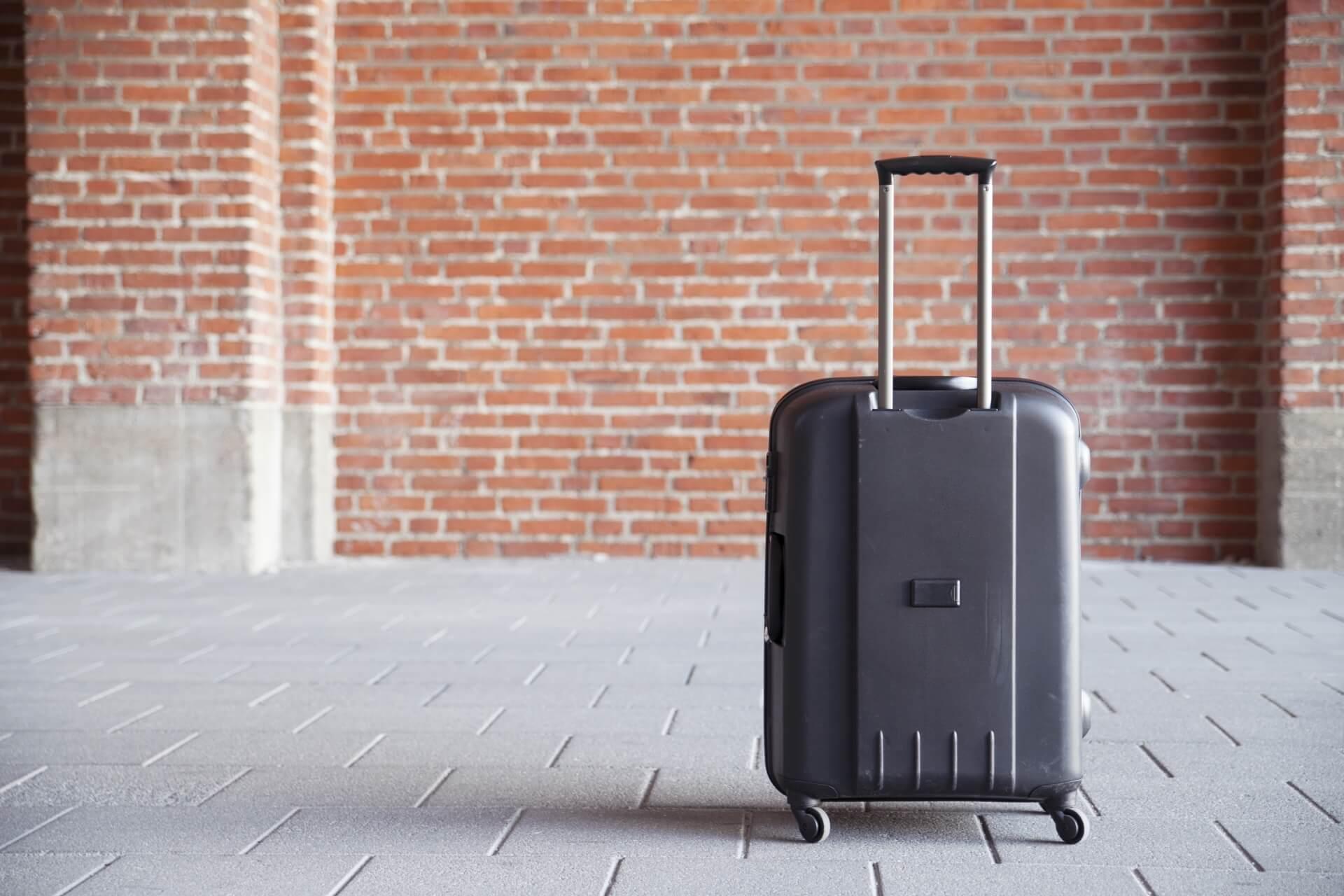 レンガの壁をバックにした伸縮(テレスコープ)ハンドルの黒いスーツケース