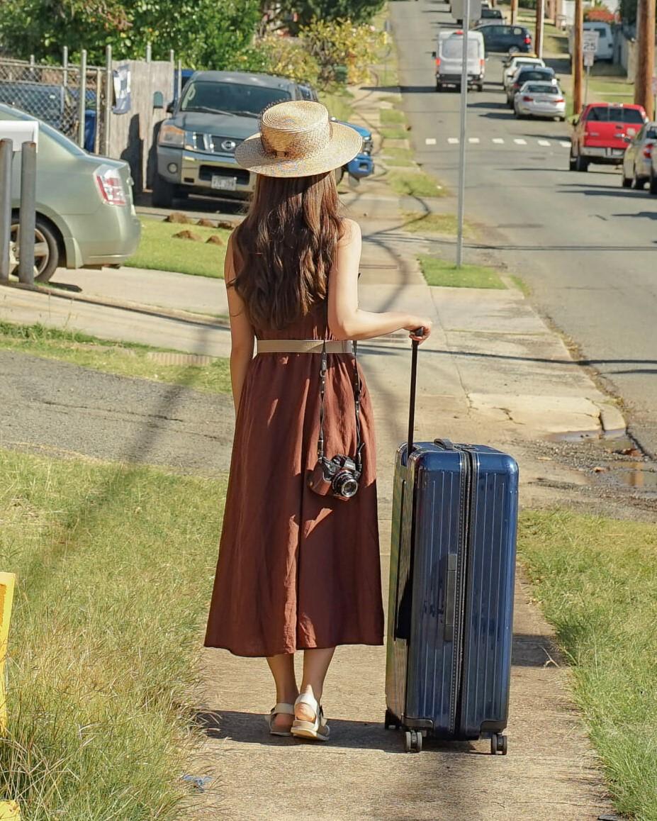 スーツケースを体の横に置き、立てたまま押して運ぶ長い髪の女性