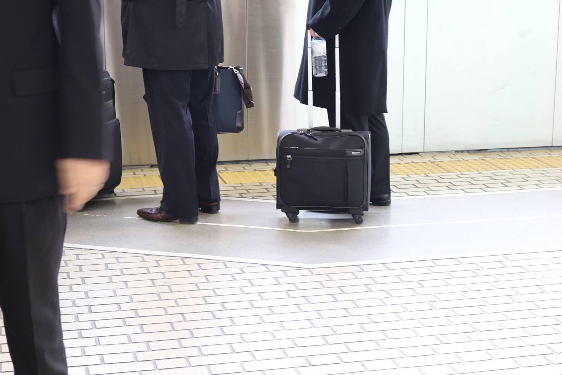 駅のホームでスーツを着た男性がスーツケースと一緒に並ぶ様子。
