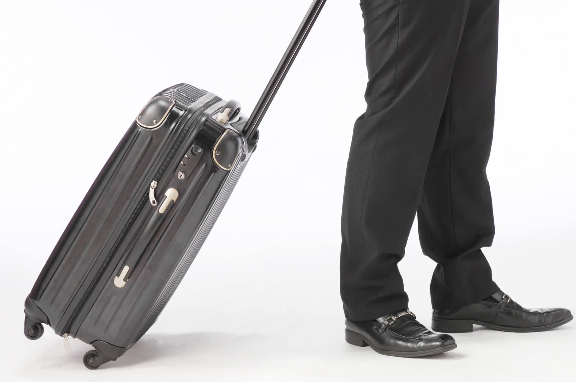 軽量なスーツケースを持って移動するビジネスマン。