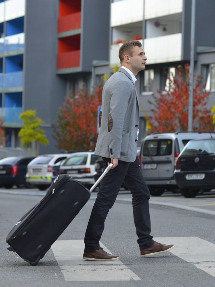 黒いソフトタイプのスーツケースを引いて横断歩道を歩く男性