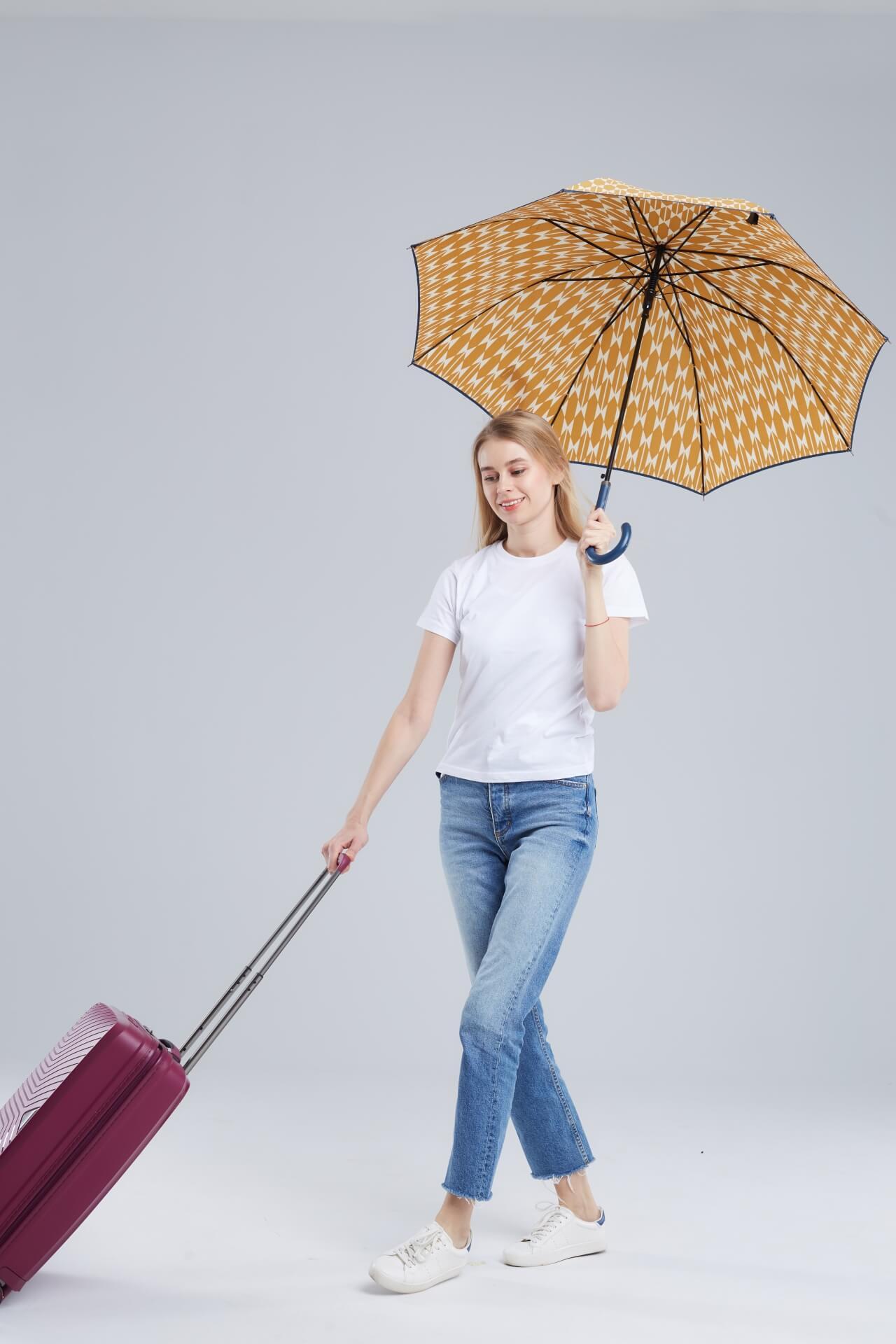傘をさして赤色のハードタイプのスーツケースをひいている女性