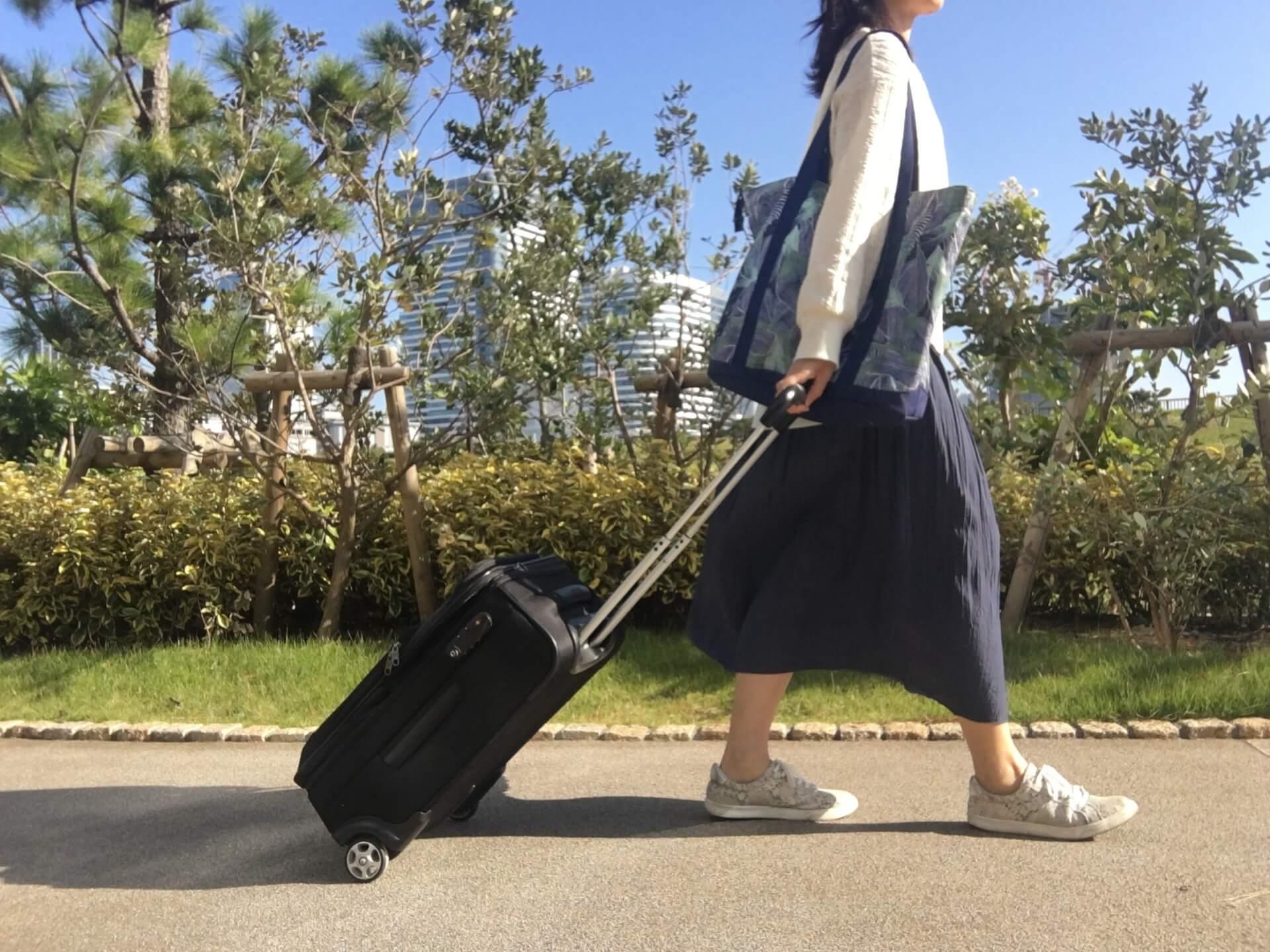 黒いスーツケースを引いて歩くロングスカートを履いた女性