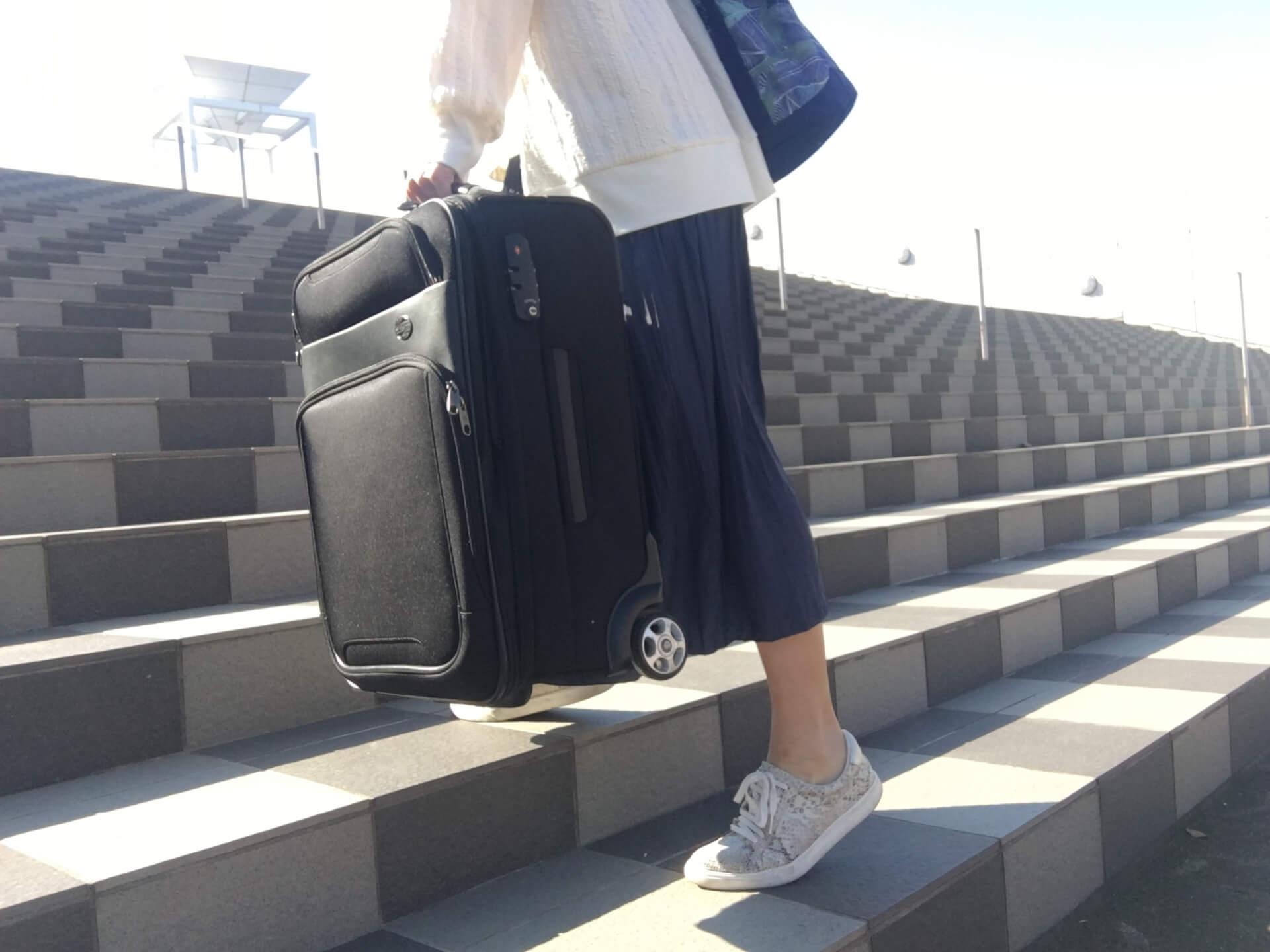 小さいスーツケースを持って階段を上るロングスカートを履いた女性