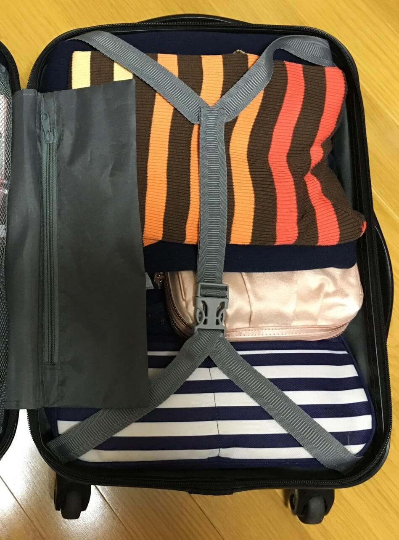 開いた状態のスーツケース。割れ物をタオルでくるんで、衣類で挟んだ状態