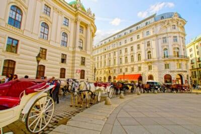 オーストリアの美しい建物の街並みと並ぶ複数台の馬車