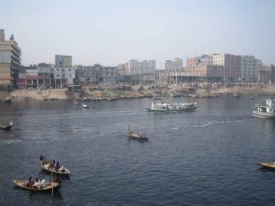 バングラデッシュの街並みと川を行きかう複数の大小の船