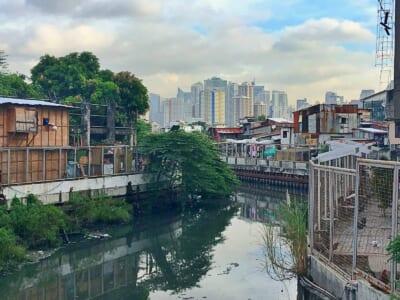 フィリピンの住宅街の間を流れるくすんだ緑色の川