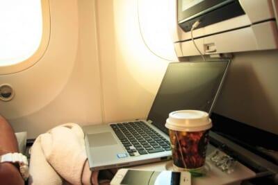 飛行機機内の席の様子。テーブルを出しパソコンと飲み物が置かれている