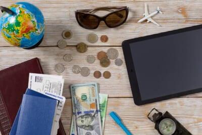 外国紙幣や硬貨や航空チケットなどが机の上に置かれた様子