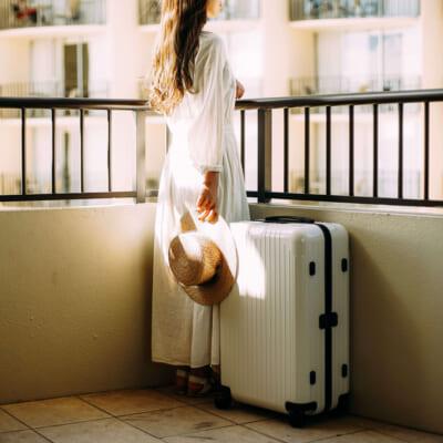 白いワンピースを着た女性とホワイトのリモワのスーツケース