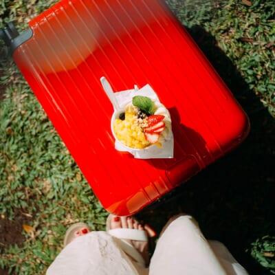 芝生の上。真っ赤なスーツケースをテーブル替わりにして載せられたパフェ